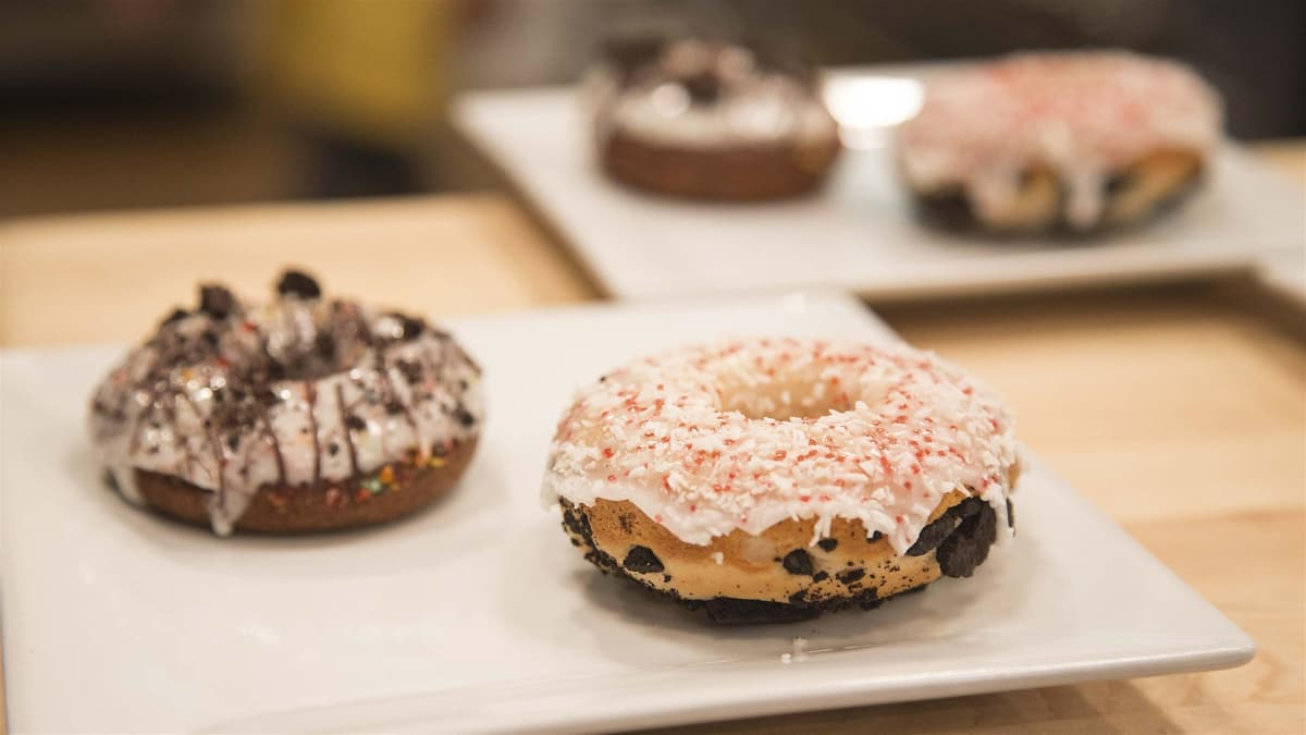 The eight kid bakers work in teams on two different types of doughnuts.